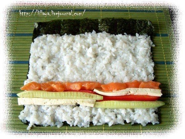 Разравниваем рис, не доходя до края 2-3 см. Затем кладем начинку. В первом случае семгу, огурец, перец, тофу,