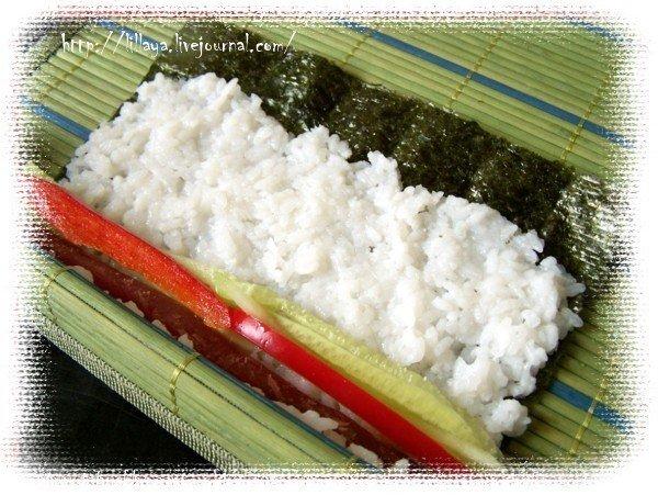 Затем, с помощью коврика сворачиваем тугую колбаску.   Дойдя до конца листа, смочить место без риса водичкой и плотно прижать. У нас должен получиться плотный ролл.  Откладываем его пока в сторонку и сделаем ролл наоборот, под названием Урамаки.