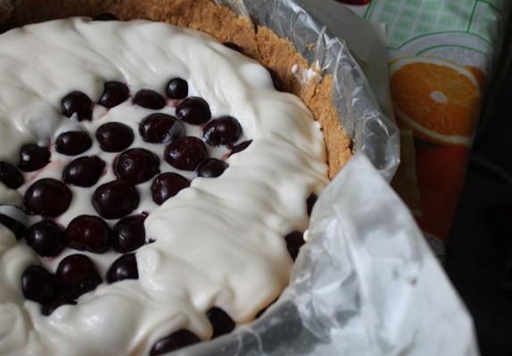 На бисквитный корж вылить немного заливки, чтобы было покрыто дно, приблизительно 1/4 всей смеси.  Сверху выложить вишню.