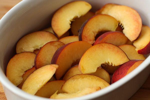 Большую форму или порционные формочки смажьте маслом и выложите туда дольки персиков в 1-2 слоя.