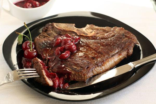 Готовый стейк положите на тарелку и дайте постоять в духовке при 50 градусах 5-7 минут. После этого подавайте, полив вишневым соусом. Хорошо также подать к такому стейку фруктовый или овощной салат и красное вино.