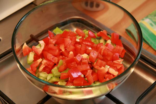 Кубиками рубим красный и зеленый перец.