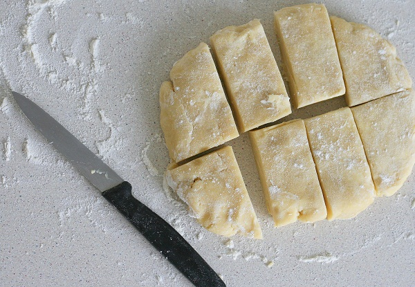 Когда тесто охладится, кладём его на посыпанный мукой стол и разделяем на 8 частей. Я просто сплющила шар в овал и разрезала ножом на части: