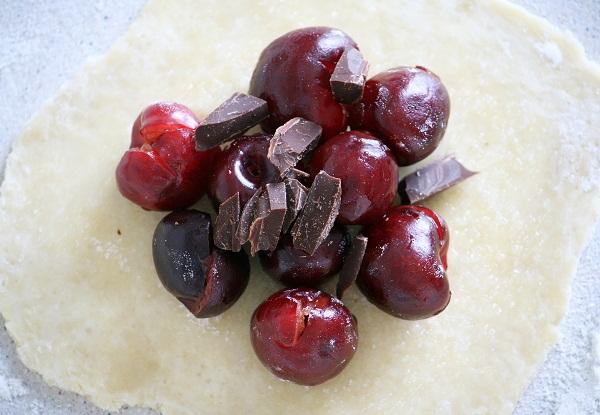 На сахар выкладываем черешню, немного, по 7-8 ягодок, а сверху присыпаем кусочками шоколада: