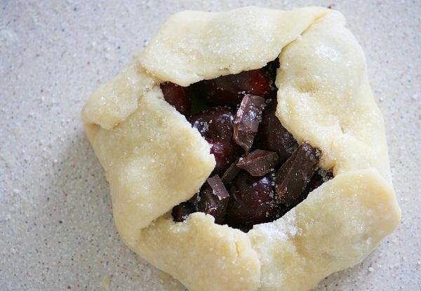 Тесто по краям приподнимаем пальцами и прижимаем к ягодам. Каждую галету смазываем смесью яйца и молока снаружи, чтобы тесто при выпечке не разлепилось, и ещё раз посыпаем сверху сахаром: