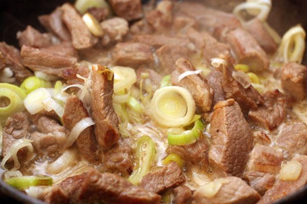 Обжарьте мясо на большом огне до образования румяной корочки. Выкладывайте мясо небольшими порциями, чтобы оно не дало сок раньше времени.  Затем добавьте нарезанный кольцами порей (белую часть), перемешайте, готовьте на среднем огне 2-3 минуты.