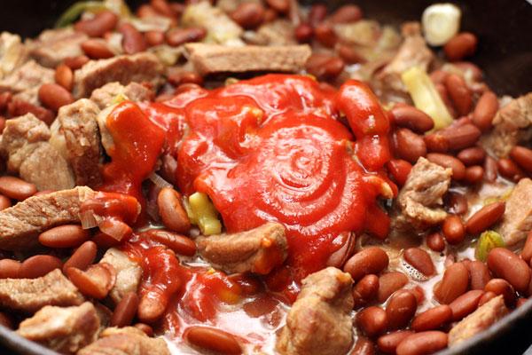Добавьте томатное пюре. Готовьте 8-10 минут на небольшом огне до готовности мяса. В процессе готовки добавьте немного жидкости от фасоли, чтобы мясо не было слишком сухим.