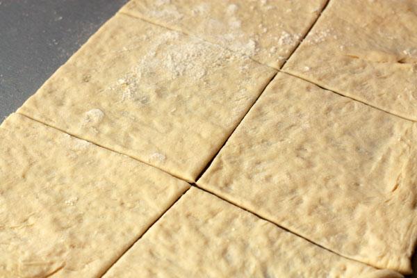 Тесто раскатайте в прямоугольник на посыпанной мукой поверхности и разрежьте на 12 прямоугольных частей.
