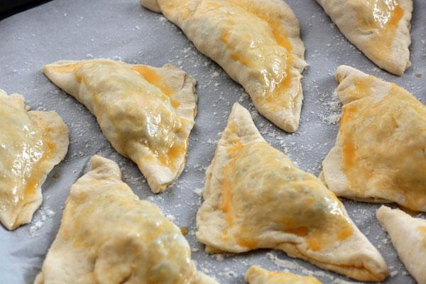 Получившиеся заготовки пирожков выложите на противень, застеленный бумагой для выпечки, смажьте яйцом и запекайте при 180 градусах 30-35 минут.