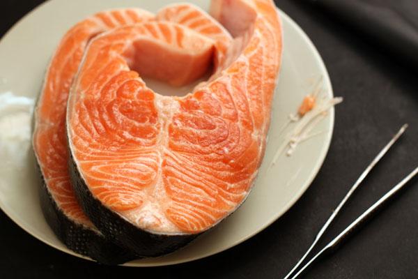 С помощью пинцета удалите из стейков семги или форели мелкие косточки.