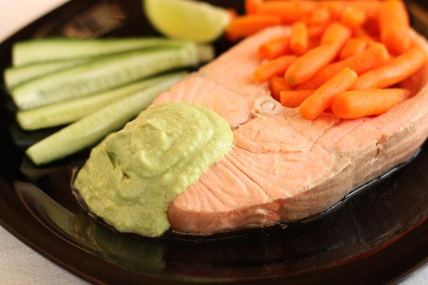С готовой рыбы снимите шкуру. Рыбу положите на тарелки. Бульон можете сохранить и использовать как основу для других блюд или соусов.  Полейте рыбу соусом, а на гарнир подайте какие-нибудь овощи, потому что блюдо очень сытное само по себе.