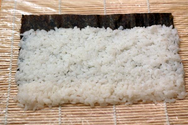 Половинку листа нори кладем на коврик для роллов, обернутый пищевой пленкой. Рис равномерно распределяем влажными руками по коврику оставляя с одной стороны свободный край нори, а с другой слой риса должен заходить за пределы нори.