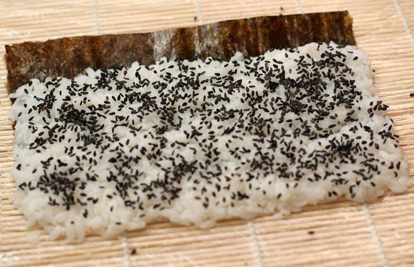 Посыпаем рис равномерно кунжутом и переворачиваем с помощью циновки макису.