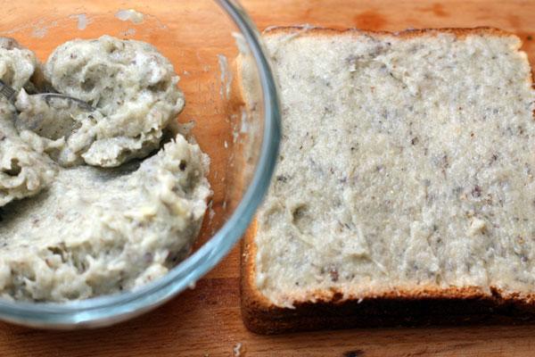 Добавьте слегка взбитый яичный белок, поперчите и посолите. Хорошо перемешайте и намажьте на хлеб для тостов слоем 3-4 мм.