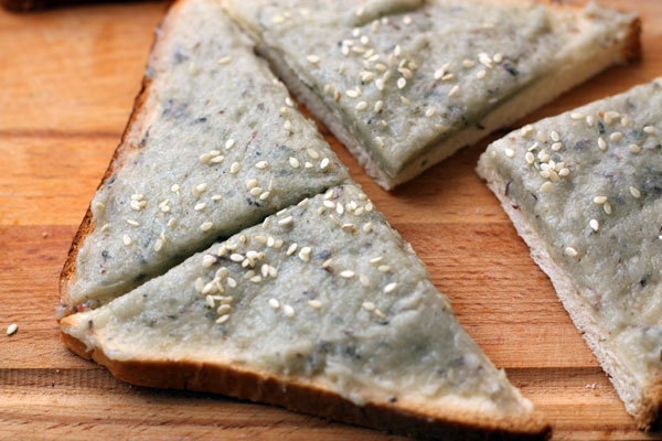 Посыпьте сверху кунжутом и разрежьте хлеб на 4 части по диагонали, чтобы получились треугольники.