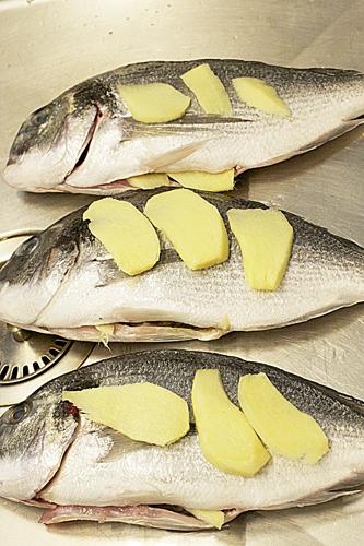 Укладываем пластинки имбиря внутрь и на бока рыбы (вариант- уложить имбирь только во внутрь,а бока натереть сметаной)