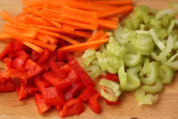 Перец нарежьте кубиками, сельдерей тонкими ломтиками, а морковь соломкой.