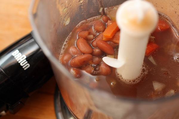 В блендер положите лук вместе с половиной овощей и фасоли из супа и бульоном.