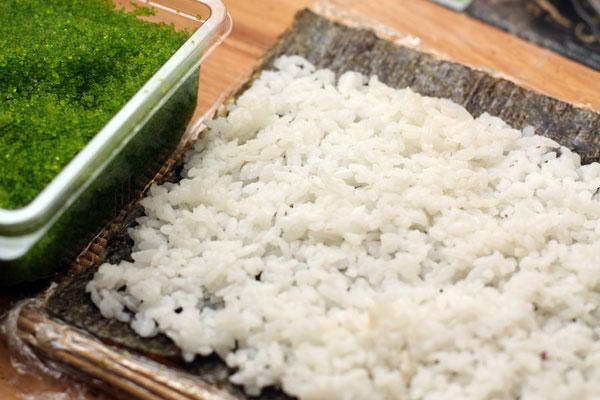 На половинку (или чуть больше) листа нори раскладываем рис ровным слоем, отступая 1-2 см от края с одной стороны.