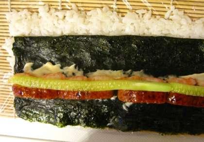 Теперь приступаем непосредственно к приготовлению роллов. Обернём макису (бамбуковую циновку для суши) пищевой плёнкой. Затем на плёнку тонким слоем (3-4 мм) выкладываем рис. По размеру площадь выкладываемого риса должна быть примерно равной половине листа нори (разрезанного поперёк перфорации). Можно для удобства сразу разрезать пополам лист нори и положить рядом – он всё равно нам потом понадобится.