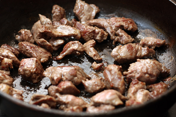 Когда мясо зарумянится со всех сторон, переложите его в толстостенную кастрюлю. Посолите и добавьте специи.