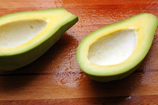 Спелый авокадо разрежьте пополам, выньте косточку и снимите шкурку.
