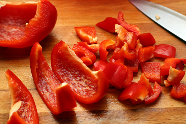 Сладкий перец очистите от семян и тоже нарежьте кубиками.