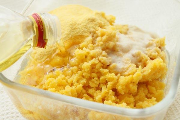 В большую миску просейте пшеничную муку, добавьте ещё кукурузной муки, положите дрожжевую закваску, остывшую кашу, масло. Влейте стакан (200 мл) теплой воды и замесите тесто с помощью миксера. Используйте специальные насадки для теста.