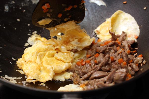 С помощью деревянной лопатки соскребите яйцо и перемешайте его с мясом.
