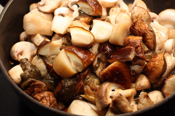 Добавьте промытые, очищенные и нарезанные белые грибы.
