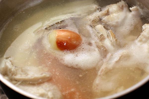 Все, кроме филе, положите в кастрюлю, залейте литром воды и доведите до кипения. Положите в бульон очищенную морковь, луковицу, соль и специи, уменьшите огонь до минимума и варите 40 минут при слабом кипении.