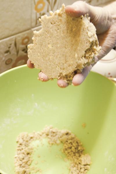 В большой миске смешиваем все остальное: муку, масло, сахар. Масло специально размягчать не надо, очень-очень хорошо все перемешиваем. Получается довольно-таки рассыпчатое тесто, но (!) если мы попробуем его собрать в лепешку, то у нас получается вот так.
