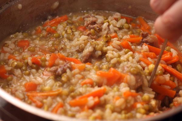 Готовьте, периодически помешивая, пока основная часть жидкости не впитается. Если к этому моменту рис готов, то выключите огонь, плотно накройте кастрюлю крышкой и оставьте на 20-30 минут.