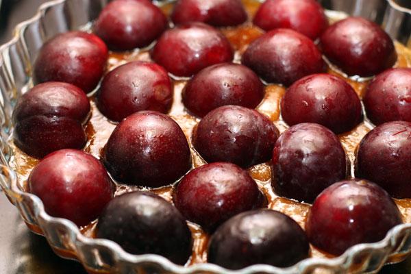 Сразу же перелейте карамель в форму для пирога и разложите сверху половинки слив.