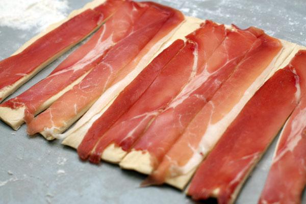 Нарезать тесто с ветчиной поперек на полоски шириной около 2 см.