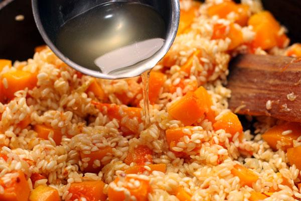 Горячий овощной бульон подливайте небольшими порциями, постоянно помешивая рис и дожидаясь полного впитывания бульона перед добавлением новой порции.