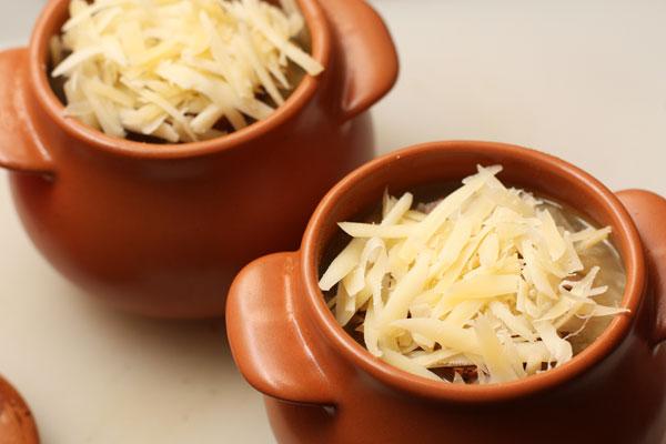 Разлейте суп по порционным горшкам, в каждый положите сверху по кусочку поджаренного багета, посыпьте сыром и поставьте в разогретую до 200 градусов духовку на 5-7 минут, чтобы сыр расплавился.