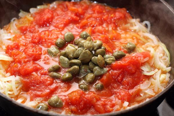 Добавьте очищенные и нарезанные мелкими кубиками помидоры и каперсы. Готовьте, помешивая, 5 минут на среднем огне.