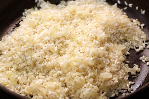Добавьте рис в сковороду, перемешайте и готовьте 2-3 минуты, пока рис не покроется маслом и не станет полупрозрачным.