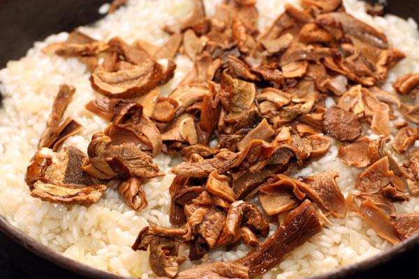 Теперь добавьте в сковороду грибы и перемешайте. Воду, в которой они замачивались, нагрейте почти до кипения, чтобы подливать в ризотто горячую жидкость.