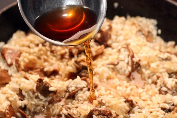 Теперь наливайте в ризотто горячую воду от грибов, постоянно помешивая. Каждый раз перед тем как добавить новую порцию жидкости дайте полностью впитаться предыдущей порции.