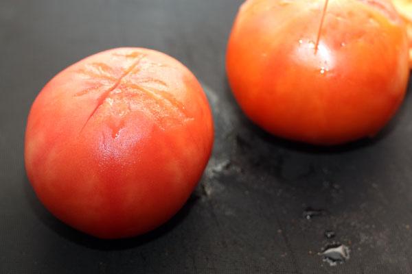 На помидорах сделайте неглубокий крестообразный надрез и опустите в кипяток на минуту. После этого снимите кожицу.