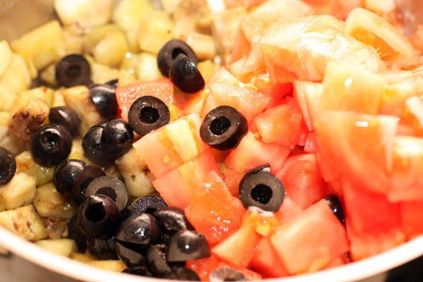 Добавьте к баклажанам нарезанные помидоры, маслины и каперсы, уменьшите огонь и тушите без крышки, пока овощи не станут мягкими.